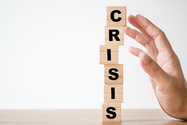 手はスクリーンの危機の言葉遣いを印刷する木製の立方体のブロックを保護します。金融および経済危機の概念。