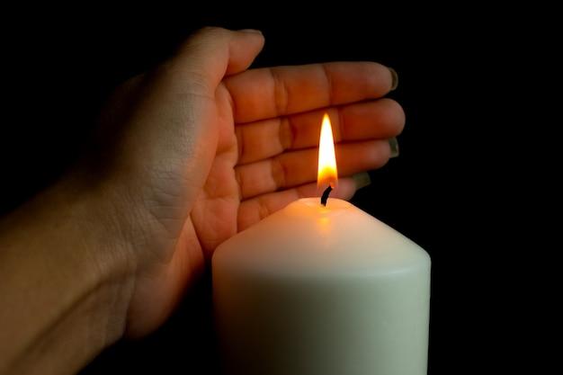 검은 배경에 어둠 속에서 바람으로부터 촛불 빛을 보호하는 손