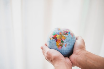 Hand protecting globe against blur background
