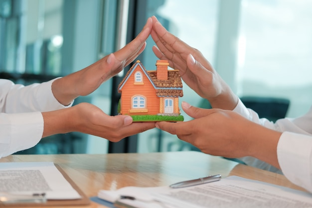 Hand protecting house model. home insurance, safety & security .