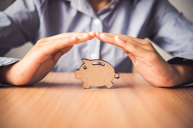 Hand protecting the icon piggy bank - the  of insurance for deposit