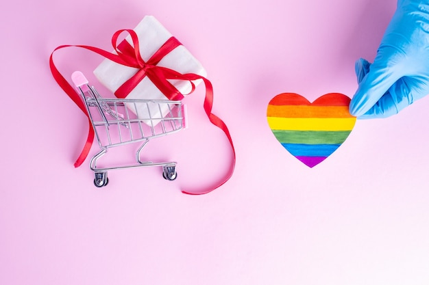 A hand in a protective blue glove holds a rainbow paper heart next to a gift in a shopping trolley on a pink background. safe holiday greetings concept. safe online shopping concept. lgbtql concept