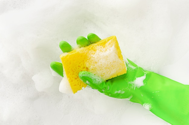 Hand in protective glove holding a soapy sponge on foam background. dish washing concept. copy space