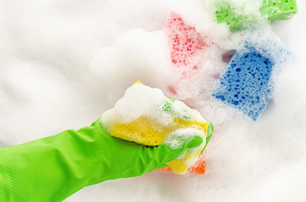 Hand in protective glove holding a soapy sponge on foam wall. housewifery concept.