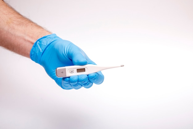 Hand in protective glove holds electronic thermometer, syringe, surgical mask, pills and flu vaccine