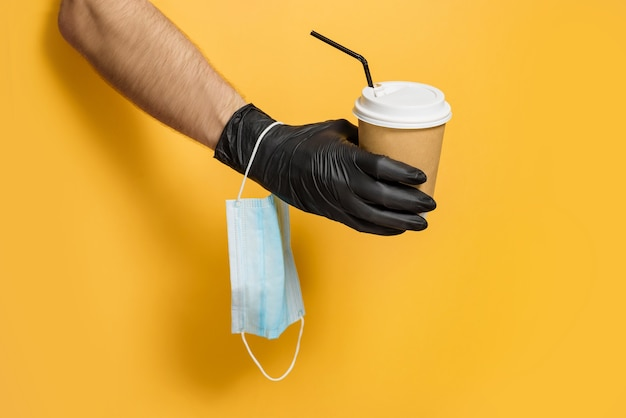 A hand in a protective glove with a medical mask on the wrist holds a paper cup on a yellow background.