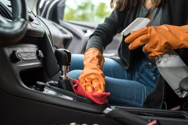 Hand in protective gloves cleaning car interior from coronavirus covid-19 using microfiber clothes. safety