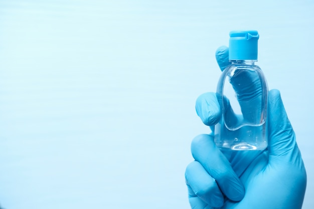 Hand in protective gloves holding hand sanitizer