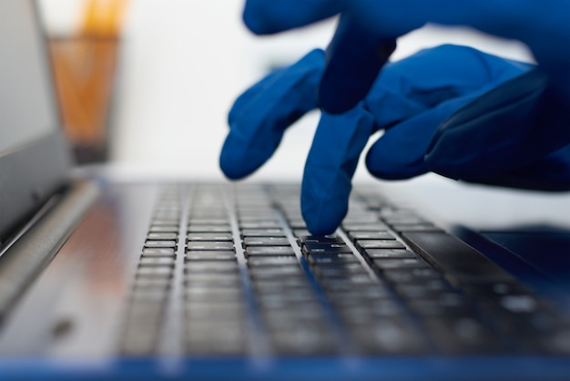 Hand in protective gloves typing on laptop keyboard. cyber crime and protection data and information concept