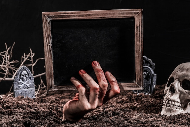 Hand protruding from grave holding blackboard
