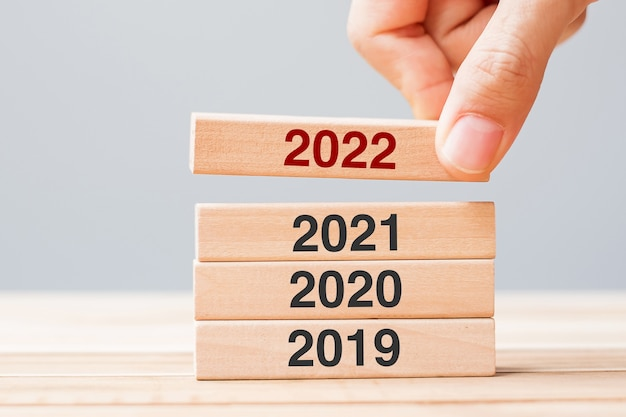 Hand pulling 2022 block over 2021, 2020 and 2019 wooden building on table background. business planning, risk management, resolution, strategy, solution, goal, new year and happy holiday concepts