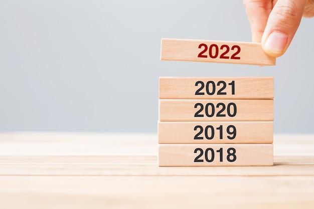テーブルの背景に2021、2020、2019の木造建築物の上に2022ブロックを手で引っ張る。事業計画、リスク管理、解決、戦略、ソリューション、目標、新年と幸せな休日の概念