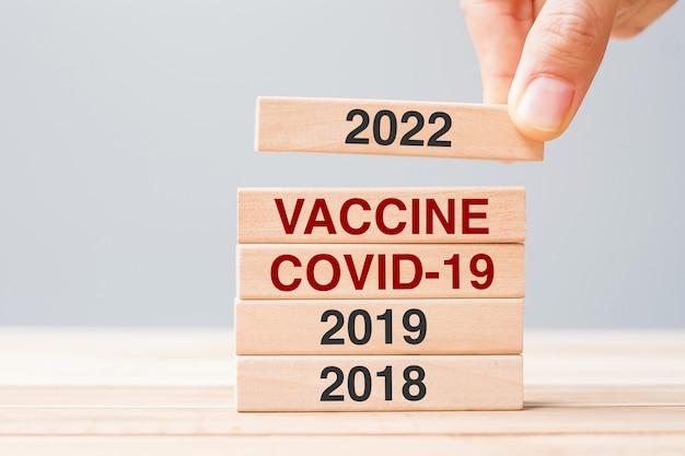Рука тянет блок 2022 года над деревянным зданием вакцины, covid-19 и 2019 года на фоне стола. кризисная экономика, вакцинация, иммунизация и пандемия коронавируса (covid-19)