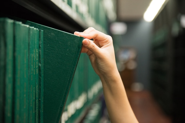 Hand pulling a thesis book off the shelf in library. green colors books.