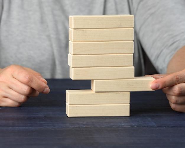 Рука вытаскивает из кучи деревянный брусок. концепция баланса, контроль ситуации, крупным планом