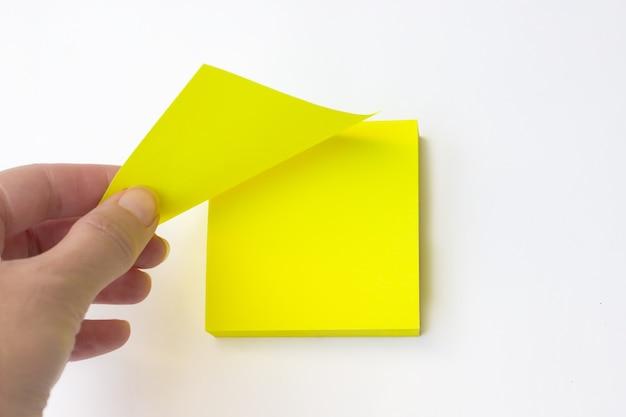 Рука стягивает желтый лист с вывешиванием. пустая желтая записка.