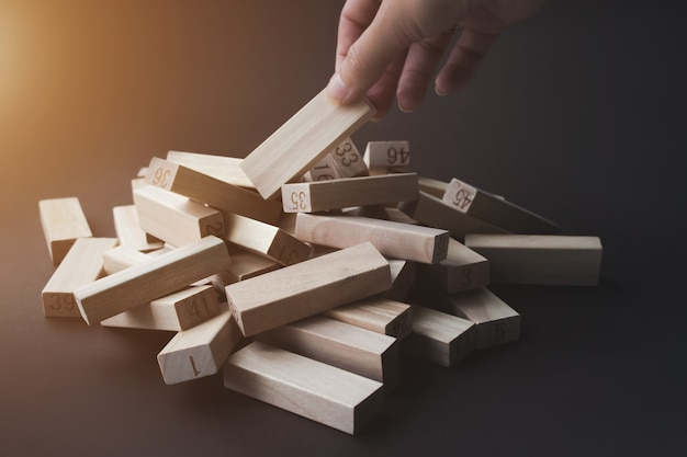 Hand pulls a wooden block from a pile of the same blocks on brown background with sunshine. leader