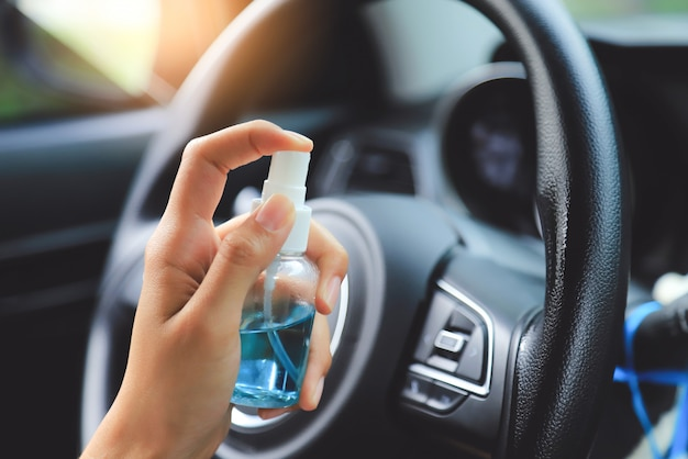 Hand pumping alcohol gel for cleaning steering wheel before using car in day time from escape vocid or corona virus. people take care living life from corona virus concept.