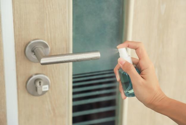 エスケープvocidまたはコロナウイルスから日中に部屋を使用する前にドアのオープナーを洗浄するためのアルコールポンプをポンプでポンプします。人々は生活を大事にする