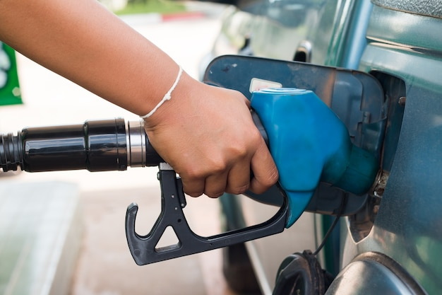 Hand pumping gas into car