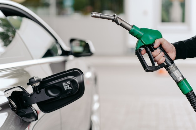 Hand pumping gasoline fuel in car at gas station