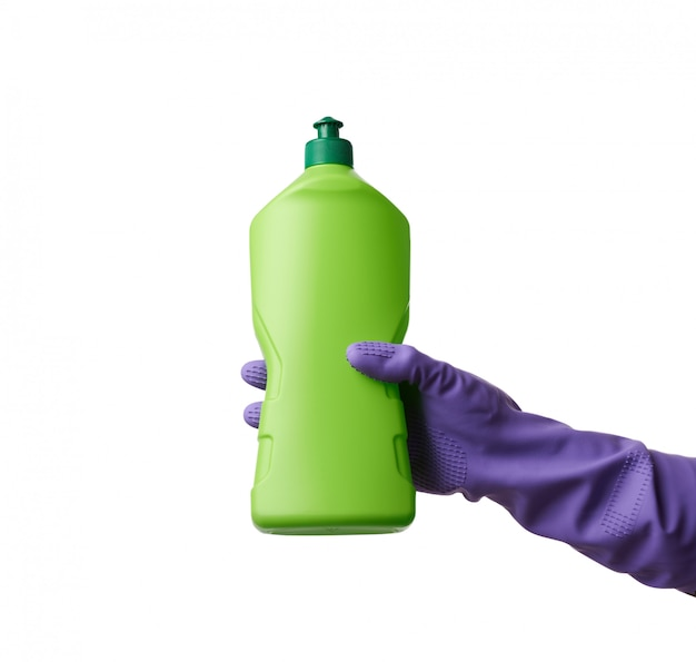 Hand in purple rubber gloves holds a green plastic bottle with d