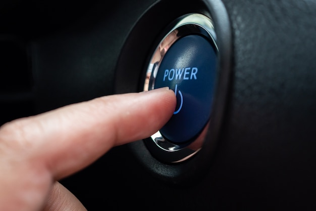 Hand push on car engine power start button close up