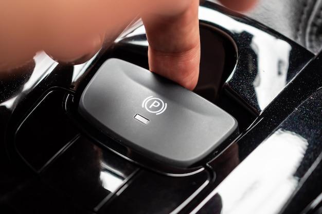 Hand push on electronic handbrake button in luxury modern car