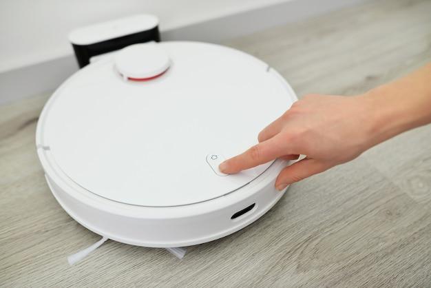 로봇 청소기의 시작 버튼을 손으로 누르십시오. 현대 스마트 가정. 버튼을 누르면 스마트 진공 로봇을 켜는 손의 세부 사항.