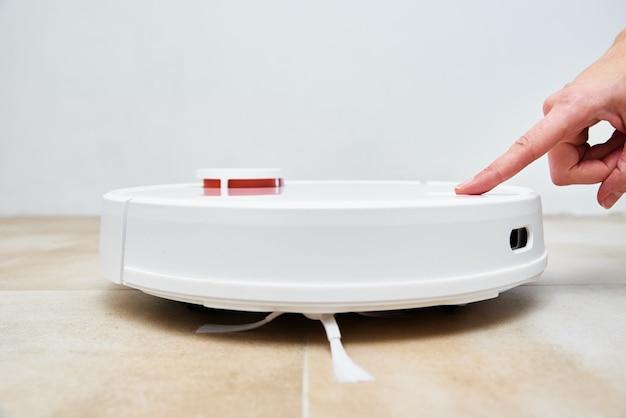 로봇 청소기의 시작 버튼을 손으로 누르십시오. 현대적인 스마트 가구