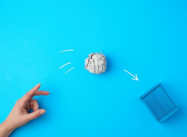 Рука сунула шар из мятой серой бумаги в металлическую корзину