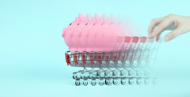Hand pushes mini cart with piggy bank on blue background. saving money for sales of the year, black friday concept.