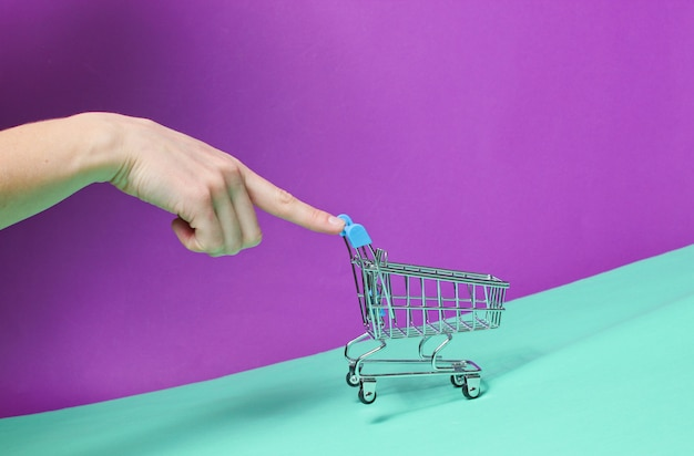 Hand pushes up sloping empty mini shopping trolley