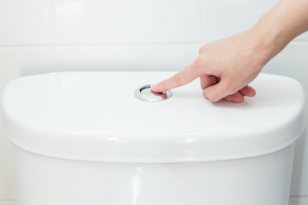 Hand pushing a button to flush