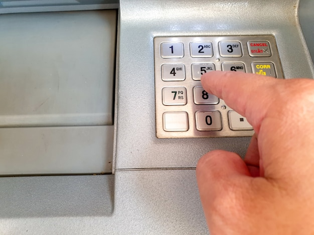 Hand pushing password numbers of atm numbers keyboard