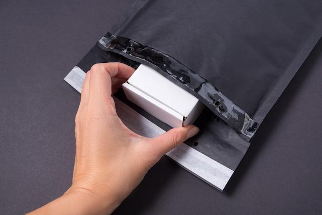 Hand put cardboard box to black paper bubble envelope