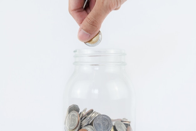 Hand put coin in to glass bottle.finance, economy concept. saving money concept.