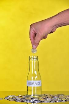Рука положить монету в бутылку со словом страхование - финансовая концепция