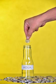 Рука положить монету в бутылку со словом медицинские - финансовая концепция