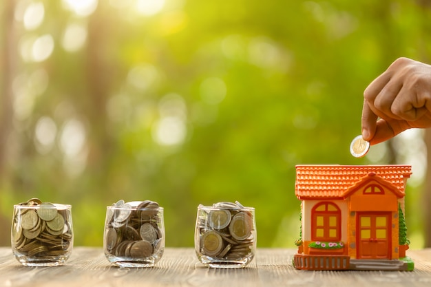 Hand put the coin to piggy bank (home model) on green nature blur background. money savings concept