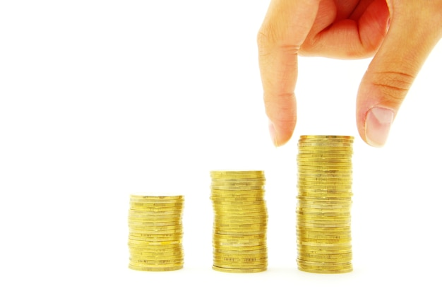 手は白い背景で隔離のお金の階段にコインを置きます