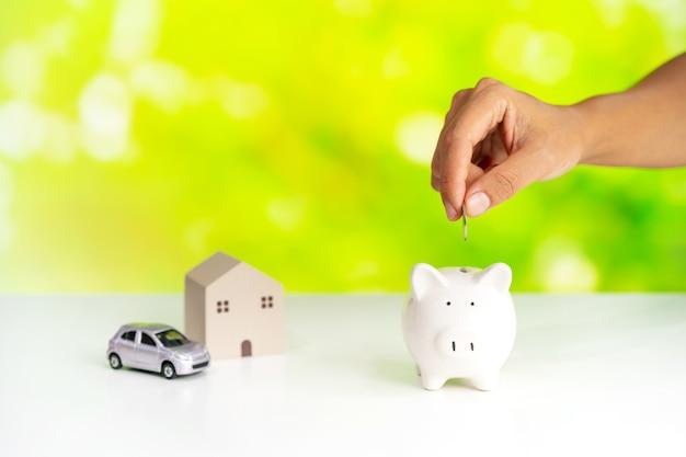 손은 녹색 자연 배경으로 돼지 저금통에 동전을 넣고 집과 자동차 개념에 돈을 절약