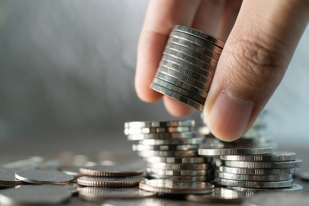 Hand put coins to stack of coins, investment and saving concept.