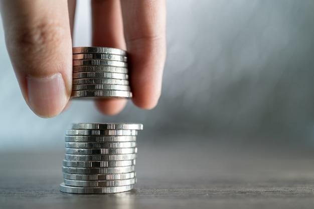 手は白い背景の上のコインのスタックにコインを置きます投資と節約の概念