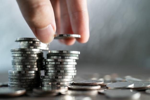 白のコインのスタックに手でコインを置きます