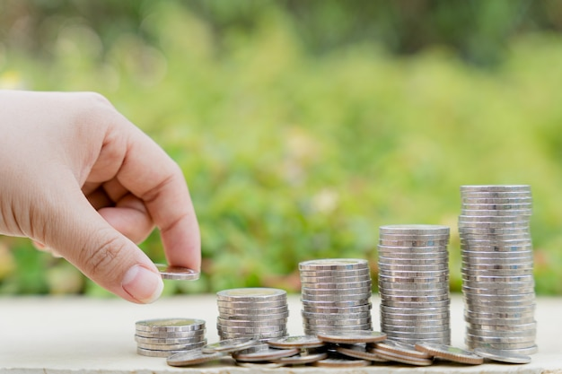 흐릿한 녹색 자연 배경의 스택 동전에 손으로 돈 동전을 넣습니다. 부동산 투자 및 주택 모기지 금융 개념입니다.