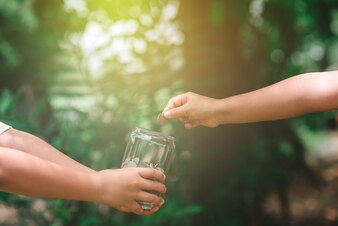 Hand put money into the glass bottle with backdrop of the green nature and sunlight.