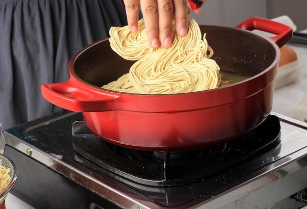 Руки положить лапшу в кипящую воду на кастрюле. приготовление лапши быстрого приготовления (ми телур). процесс приготовления на кухне