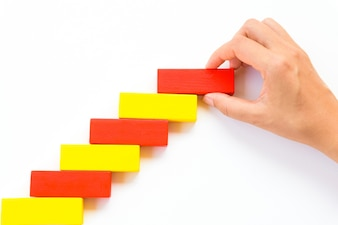 Hand put red wooden block on yellow wooden blocks in the shape of a staircase