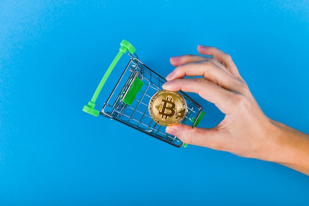 Hand puts bitcoins in a shopping cart on a dark blue